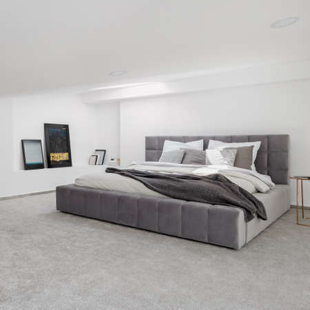 Simple bedroom interior with white walls and ceiling and gray carpet flooring and with big, gray quilted bed and art Imagens