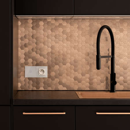 Stylish black faucet with golden sink, in elegant kitchen with black furniture and golden hexagonal backsplash wall tiles