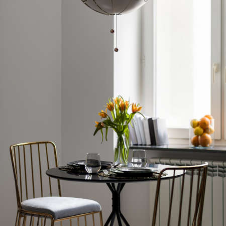 Elegant, black dining table with two, modern gold chairs and tableware with flowers in vase on the table Imagens - 157357260