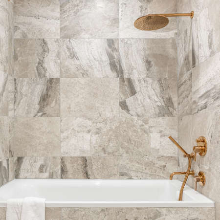 Stylish bathroom with big white bathtub and beige marble style tiles, copper tap and shower