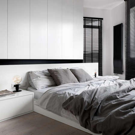 Designed bedroom with white wardrobe, bedside table and big bed, gray bedclothes, wooden floor and black window blinds