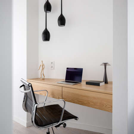 Simple wooden desk with drawers in home office room with comfortable chair and ceiling lighting