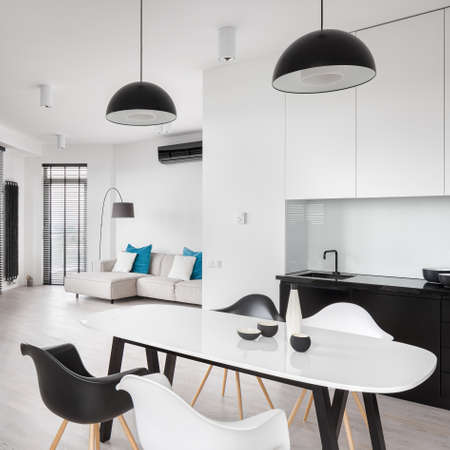 Elegant, black and white apartment interior with kitchen and dining area open to living room Imagens - 157475847