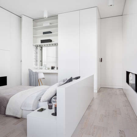 Stylish white bedroom with big bed, fancy dressing table in wardrobe and wooden floor