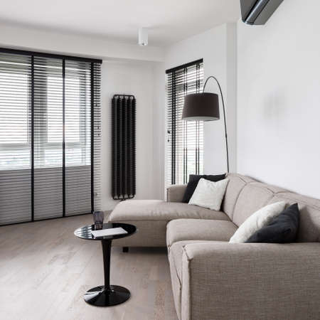 Simple and elegant living room with beige couch, black coffee table, wooden floor and long, black blinds in big windows