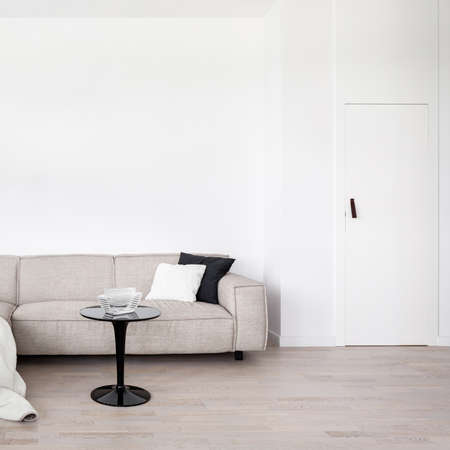 Living room with white wall and door, beige sofa and black modern coffee table Imagens