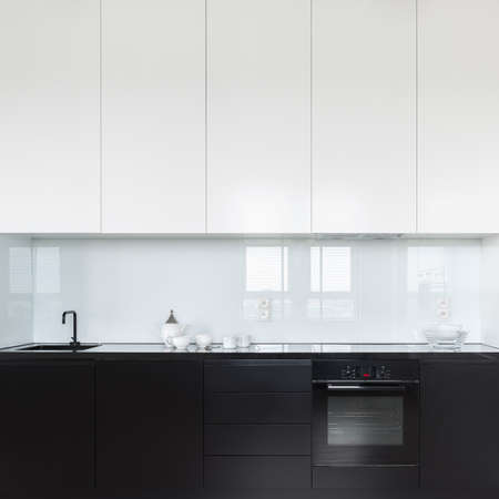 Elegant and simple kitchen with black lower drawers, cupboards and countertop and white higher cupboards