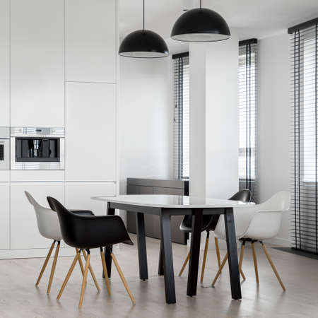 Stylish black and white dining area with modern table and four chairs under two black pendant lamps Imagens