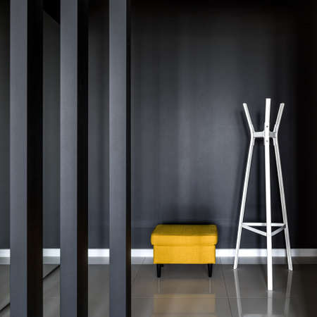 Luxury and simple corridor interior with modern black wall, white clothes hanger and yellow ottoman seat
