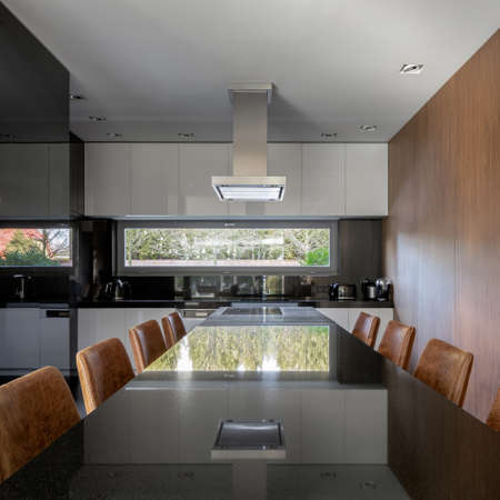 Luxury long dining table for eight with black gloss countertop in stylish kitchen with wooden wall Imagens
