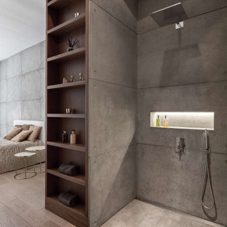 Modern designed bathroom with shower open to bedroom, both with stylish concrete wall tiles and wooden shelves in the middle