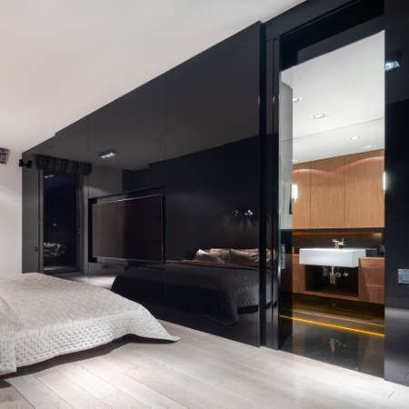 Luxury bedroom with black mirrored wall with television screen and open doors to elegant bathroom Imagens