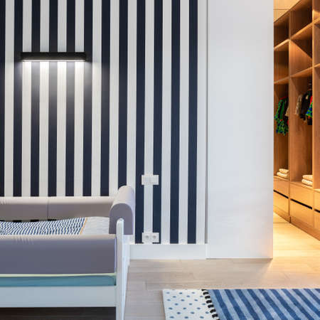 Child bedroom with wall in blue stripes and big wardrobe with wooden shelves and lights on above bed