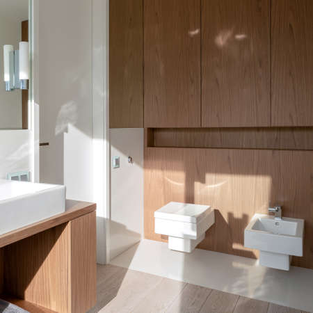 Bright bathroom with sunlight, wooden furniture and white, square toilet and bidet