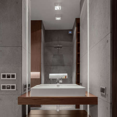 Stylish bathroom with concrete wall tiles, big mirror above white washbasin with led light and wooden elements Imagens