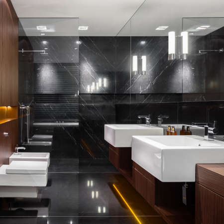 Dark marble and wood in elegant bathroom with shower behind glass wall Imagens - 157526049