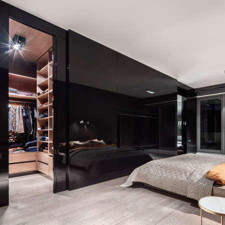 Luxury bedroom with walk in closet with wooden shelves behind stylish, black and mirrored wall