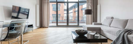 Spacious loft living room in loft style apartment with big windows to balcony and wooden floor