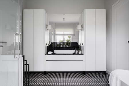 Stylish black and white bathroom with two wardrobes, white cabinet under modern washbasin and modern floor tiles
