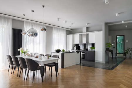 Fancy white kitchen with long, decorated dining table with gray chairs and stylish wooden floor Imagens
