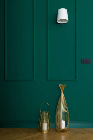 Beautiful emerald green wall with molding and two, golden decorative candlesticks on wooden floor