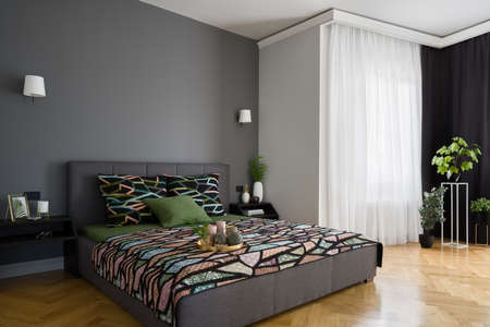 Beautiful bedroom with big bed, modern gray wall and elegant wooden floor, window behind long curtains and many stylish decorations Imagens