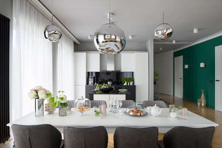 Beautiful decorated elegant dining table with stylish chairs, under silver chandelier in apartment with open kitchen and green wall Imagens