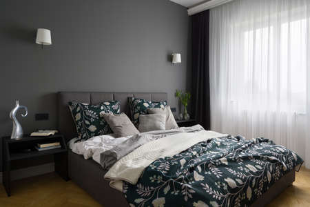 Elegant and stylish bedroom with gray wall, big comfortable bed and big window behind white curtains