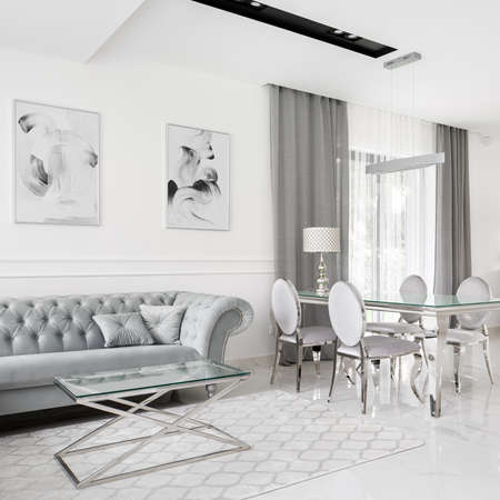 Exclusive living room with stylish sofa, coffee table and dining table with chairs all in white, silver and gray Imagens