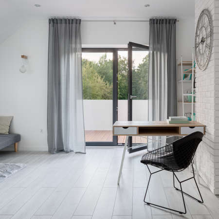 Simple desk to study in bright room with window doors open to balcony
