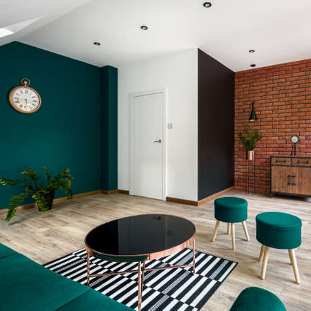 Stylish living room with two decorative walls, one in red brick and one in emerald green