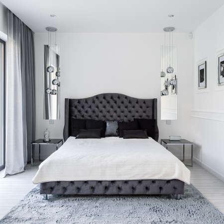 Glamor style bed with gray quilted frame and headboard in white silver and gray bedroom Imagens