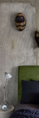 Vertical panorama of stylish bedroom with concrete wall and african masks behind big bed with green velor headboard