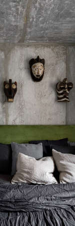 Vertical panorama of modern bedroom with bare concrete on wall and ceiling, decorative african style masks and green velor on bed headboard