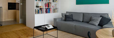 Panorama of apartment with kitchen behind white bookcase in stylish living room with pine wood floor, big gray couch and black coffee table