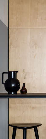 Vertical panorama of simple black table with decorative vase and dish, tall bar stool under it and wooden cupboards in background