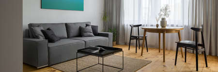 Panorama of small and stylish living room with gray couch, black coffee table and round, wooden dining table with two black chairs