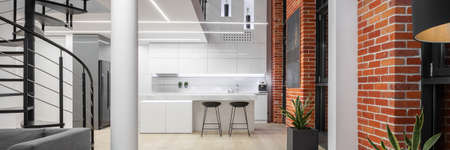 Panorama of spacious loft style apartment with white kitchen, red brick on the walls and black stairs to top floor