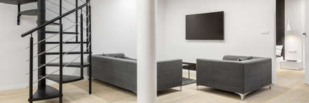 Panorama of white living room with black, spiral stairs, white pillar and wooden floor