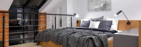 Panorama of modern bedroom on mezzanine in loft style apartment with big window and brick wall at night