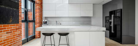 Panorama of stylish kitchen in loft apartment with white furniture, red brick on the walls and big window Imagens