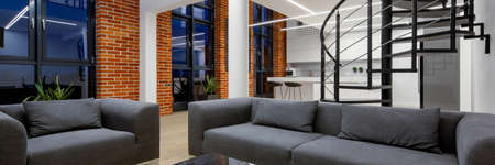 Panorama of loft apartment with living room open to kitchen, spiral stairs, brick walls and big windows