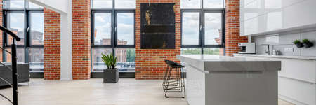 Panorama of luxury white kitchen in stylish loft apartment with exposed brick on the walls and big windows