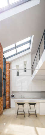 Vertical panorama of amazing big windows in loft style apartment with white spacious kitchen, exposed red bricks on the walls and mezzanine Imagens