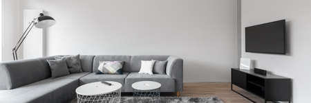 Panorama of simple and elegant living room with white walls, big corner sofa, modern coffee tables and big tv screen