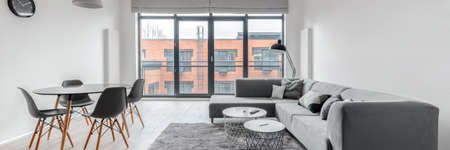 Panorama of modern apartment with window wall in stylish living room with dining area for four and big, gray corner sofa