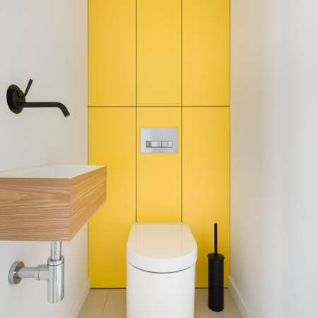 Modern design bathroom interior with black tap in small washbasin and white toilet with rectangular yellow wall tiles behind it