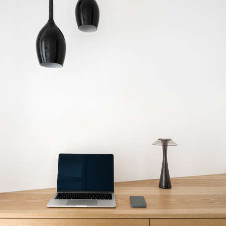 Close-up on wooden corner desk with drawers in home office area under black ceiling lamps