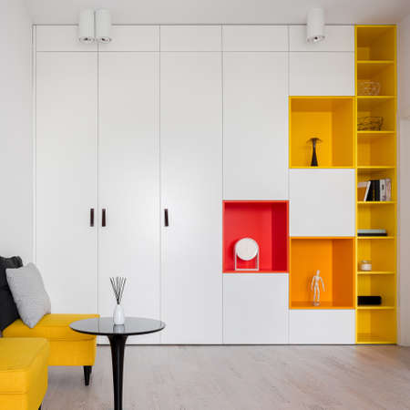 Modern designed room with yellow, red and orange shelves in stylish, white wardrobe