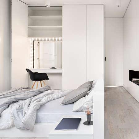 Elegant bedroom with big bed, wooden floor and dressing table with mirror and lights on in wardrobe